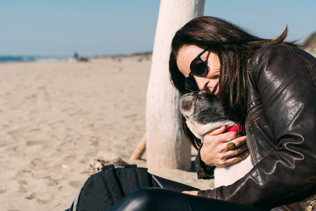 Woman hugging boston terrier at the beach